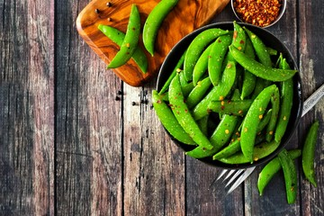 Bowl of healthy roasted snap peas. Top view, corner orientation with copy space on a rustic dark wood background.