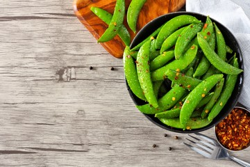 Bowl of healthy roasted snap peas. Top view, corner orientation with copy space on a wood background.