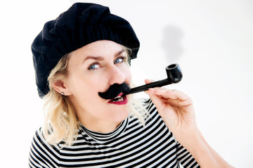 blond woman as french man with beret, mustache and pipe