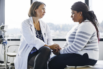 Mature female doctor holding hands while talking with patient in hospital exam room
