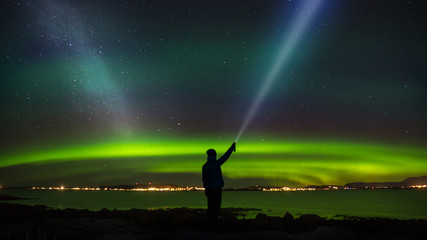 Woman standing with headlamp in the tide looking at nightsky, milky way and aurora.