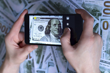 phone in hand, picture of dollar, on the background of dollars