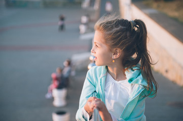 cute smiling little girl wearing turquoise blouse outoors in spring in sunset