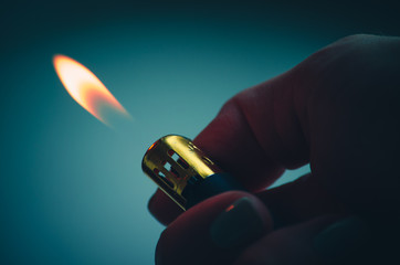Lighter finger burning fire on green blue background