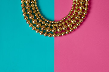 Golden beads on pink blue background