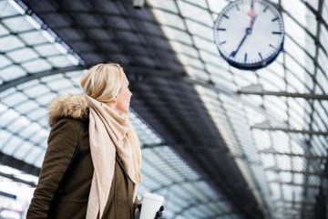 Frau schaut auf Uhr im Bahnhof weil ihr Zug Verspätung hat