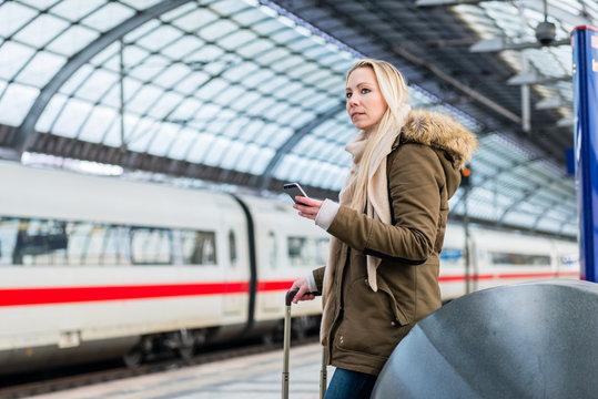 Frau im Bahnhof nutzt die Fahrplan App während der Zug einfährt