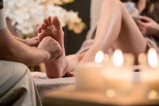 Woman having reflexology foot massage in wellness spa