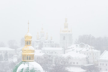 Metal Orthodox cross on the background of winter storm. Snow covered cupola of Lavra in Kiev. Ukrainian landmark.