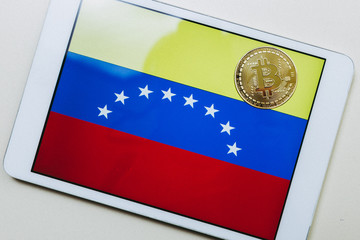Close up view of a tablet with flag of Venezuela and a bitcoin gold on it