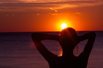 Silhouette of a girl while enjoying ocean scenery in sunset / sunrise time.