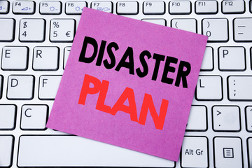 Handwriting Announcement text showing Disaster Plan. Business concept for Emergency Recovery written on sticky note paper on the white keyboard background.