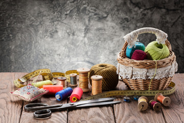 tbundles of thread in the basket, scissors and thread in drums on the wooden table of the table