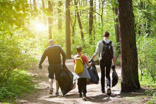 Recycle waste litter rubbish garbage trash junk clean training. Nature cleaning, volunteer ecology green concept. Young men and boys pick up spring forest at sunset . Environment plastic pollution