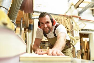 fröhlicher Tischler schleift Holzbrett an einer Maschine in Schreinerei // carpenter works in a joinery - workshop for woodworking and sawing