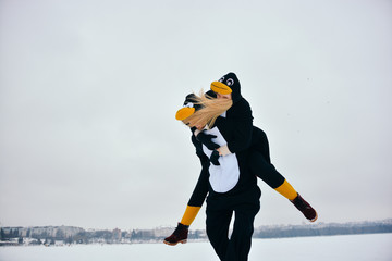 Young couple in the penguin costumes are have fun on snow. Happy Loving Couple