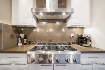 Stove closeup in modern kitchen interior with stainless steel gas cook-top.