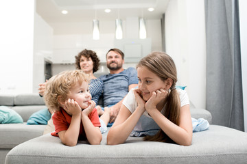 Portrait of happy family with two kids enjoying evening watching TV together sitting on sofa in living room, focus on brother and sister in foreground