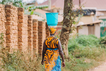 woman carrying bucket on her head in Uganda Wall mural