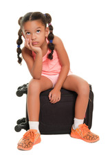 Small girl sitting on a suitcase looking bored and impatient - Isolated on white