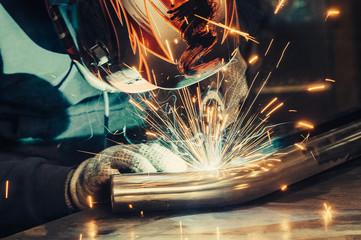 Welder in mask welding metal and sparks metal. Toned image.