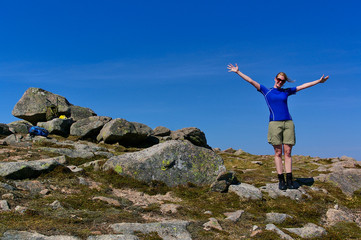 Blond girl with sunglasses wearing athletic clothes on a rocky summit on a sunny day