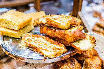 Closeup pile stack of many french toast savory sweet egg bread slices fried on serving tray in home bakery shop, store, cafe
