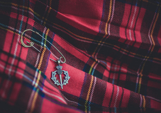 A vintage brass thistle pendant on a pin against the background of a traditional scottish kilt. Symbols of Scotland. Selective focus.