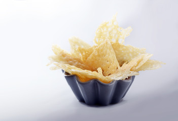 crisp parmesan cheese chips, finger food party snack or appetizer in a bowl on a light gray background, copy space