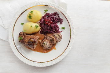 beef roll with red cabbage and potatoes, german meat roulade stuffed with cucumbers, bacon and onions on an elegant gold rim plate on a white wooden table, high angle view from above, copy space
