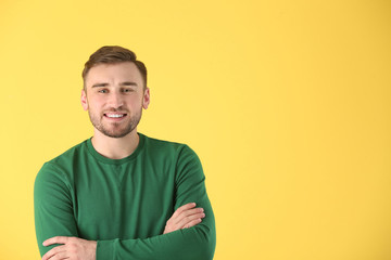Young man in casual clothes on color background