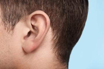 Young man, closeup of ear. Hearing problem Wall mural