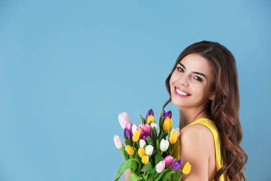 Beautiful woman holding bouquet of tulips on color background