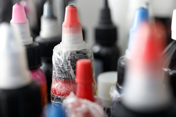 Many bottles with ink in tattoo salon, closeup