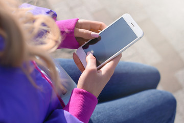 Woman with mobile phone outdoors, closeup