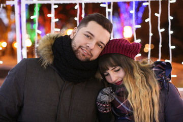 Portrait of young loving couple outdoors on Christmas eve