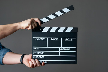 A movie production clapper board. Hands with a movie clapperboard on grey background with copy space, close-up.