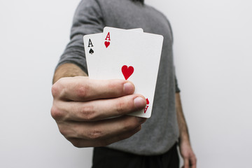 Man holding two plastic cards(aces)