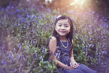 Portrait of cute girl sitting amidst flowering plants at park