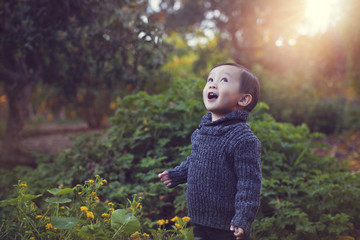 Cute playful baby boy with mouth open standing against plants at park