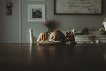 Girl taking food from plate on dining table at home