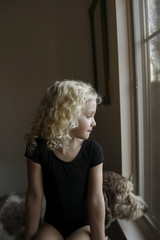 Girl with dog looking through window while sitting at home