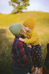 Cropped image of boy by mother and brother kissing on field