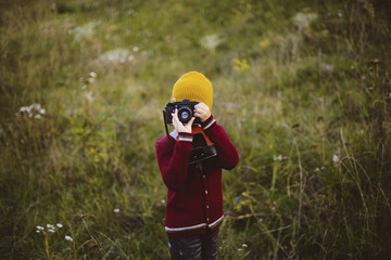 Boy photographing with camera while standing on grassy field