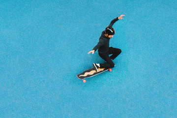 High angle view of man skateboarding on blue floor at skateboard park