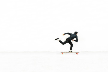 Side view of man skateboarding against white wall