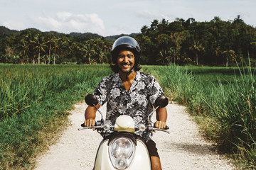 Portrait of smiling man riding motorcycle on dirt road against sky