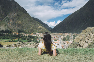 Rear view of female male hiker looking at village while sitting on mountain against sky at Pisac