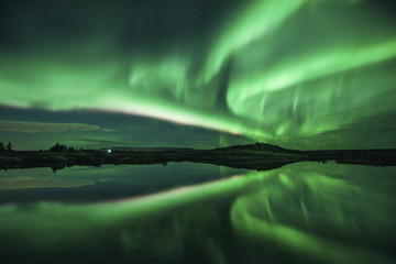 Majestic view of aurora borealis over lake at night
