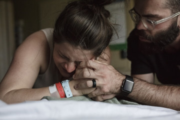 Close-up of man comforting painful pregnant woman on hospital bed